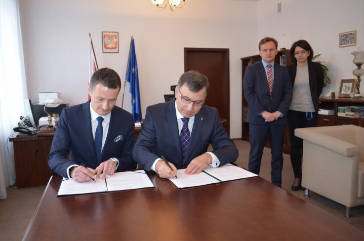 Zbigniew Jagiełło - prezes zarządu PKO Banku Polskiego oraz Radosław Stępień wiceprezes Zakładu Ubezpieczeń Społecznych siedzą przy stole i podpisują porozumienie.